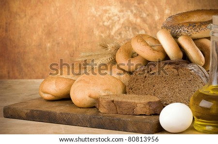 bakery products and wheat grain on wooden texture - stock photo
