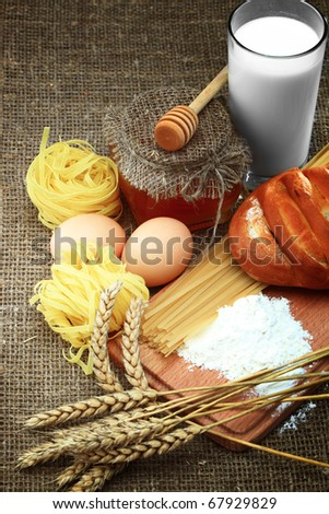 Bakery products, eggs and milk against sacking - stock photo