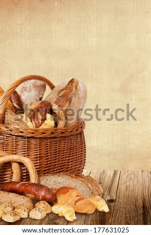 Bakery products in wicker basket and on a wooden table.