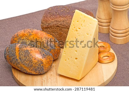 Bakery products (rye bread, buns, bagels)  and cheese on a cutting board - stock photo