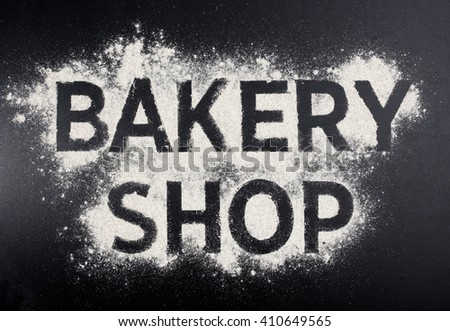 Bakery shop word made of flour on black table.