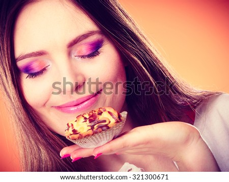Bakery sweet food and people concept. Content attractive woman closed eyes holds cake cupcake in hand smelling orange background - stock photo