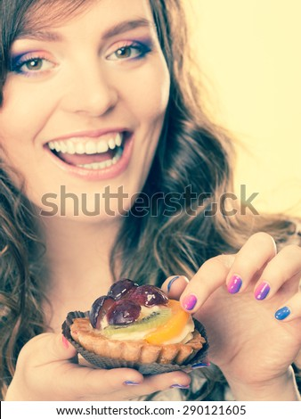 Bakery, sweet food and people concept. smiling cute woman curly hair holding fruit cake cupcake in hand yellow background