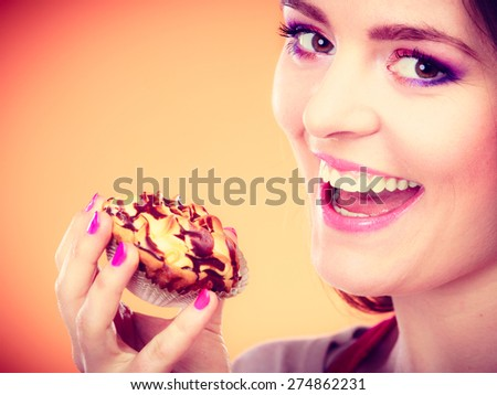 Bakery sweet food and people concept. Smiling woman holds cake cupcake in hand orange background - stock photo