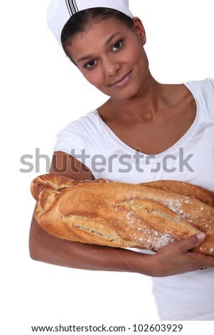 Bakery worker holding bread - stock photo