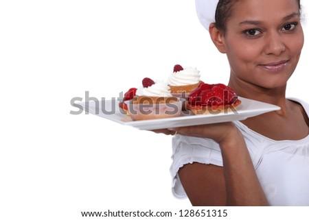 Bakery worker holding plate of fruit tarts - stock photo