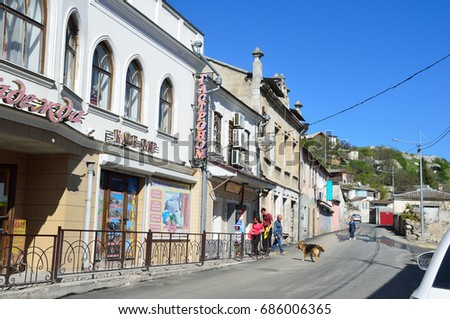 Bakhchisaray, Crimea, Russia, April, 30, 2017.People walking near old houses on the street of Roza Lyuksenburg in Bakhchisaray in sunny day