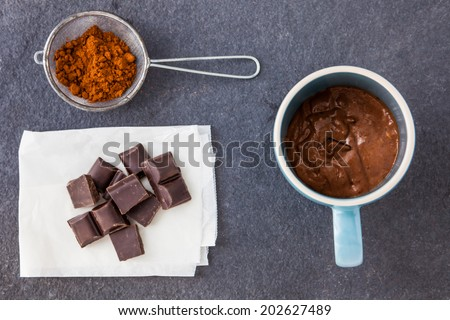 Baking a chocolate cake in a mug - mixed dough with chocolate chips in a cup ready for cooking with cocoa powder and chunks of chocolate ion a slate background