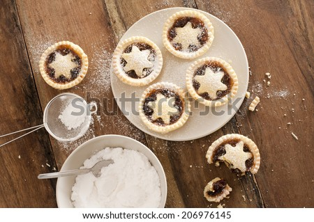 Baking a plate of tasty traditional Christmas mince pies with decorative pastry stars sprinkled with icing sugar, view from above on a wooden kitchen counter - stock photo