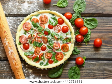 Baking a vegetables tart  with tomatoes and spinach. The ingredients on the table - dough, tomatoes, spinach, cream, eggs  - stock photo