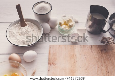 Baking background. Cooking ingredients for dough and wooden board on white rustic wood. Top view with copy space, recipe or culinary classes.