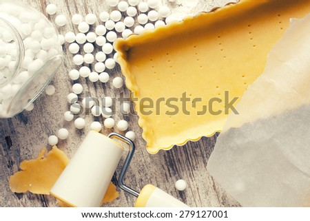 Baking background. Ingredients for dough bottom for tartlet, quiche, tart.  Shortbread dough, baking forms, ceramic baking beans, rolling pin.  Top view. Retro style toned.  - stock photo