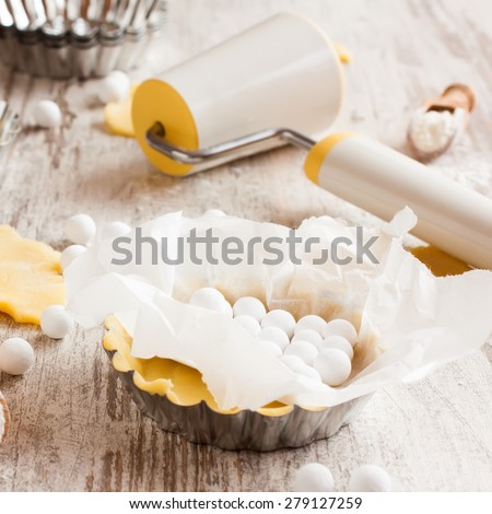 Baking background. Ingredients for dough bottom for tartlet, quiche, tart.  Shortbread dough, baking forms, ceramic baking beans, rolling pin.  Top view. Selective focus. - stock photo
