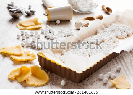 Baking background. Ingredients for dough bottom for tartlet, quiche, tart.  Shortbread dough, baking forms, ceramic baking beans, rolling pin.  Selective focus. - stock photo