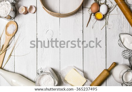 Baking background. Ingredients for the dough - Milk, eggs, flour, sour cream, butter, salt and different tools. On a white wooden background. Free space for text . Top view - stock photo