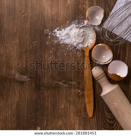 Baking background with eggshell, flour and rolling pin on wooden vintage table. Tabletop view. - stock photo