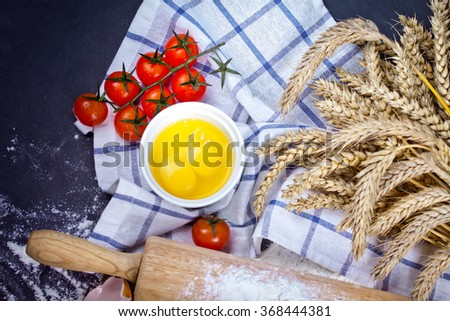 Baking background with eggshell, flour and rolling pin. Pizza cooking ingredients. Selective focus. - stock photo