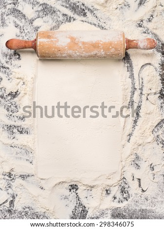 baking background with flour and rustic rolling pin. Top view, place for text. - stock photo