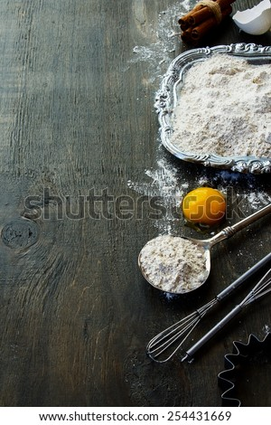 Baking background with raw eggs, eggshell, cinnamon and flour. Wood background. - stock photo