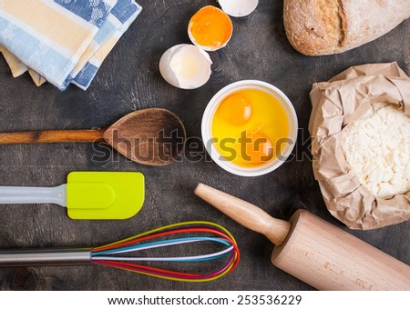 Baking background with utensils, napkin, eggshell, bread, flour, rolling pin. Vintage wood table from above. Rustic background  - stock photo
