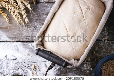 Baking bread. Dough in proofing basket on wooden table with flour, cumin and wheat ears. Top view. - stock photo