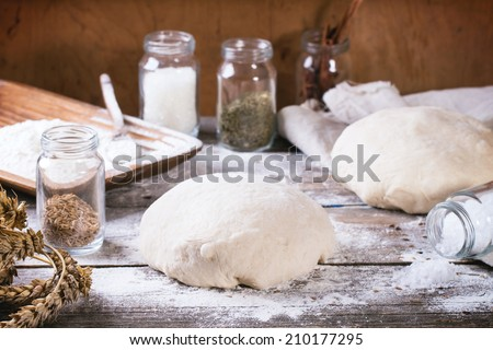 Baking bread. Dough on wooden table with flour, rolling-pin and jars with backing ingredients. See series - stock photo