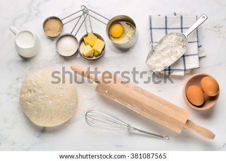 Baking cake, dough recipe ingredients (eggs, flour, milk, butter, sugar) on white table.  - stock photo