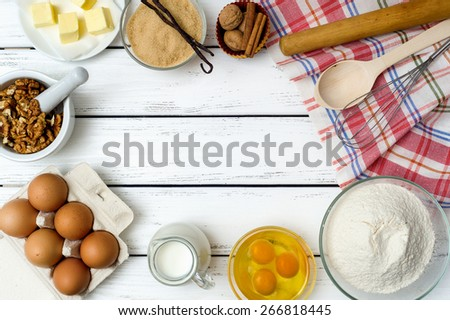 Baking cake in rural kitchen - dough recipe ingredients (eggs, flour, milk, butter, sugar) on white wooden table from above. With copy space.