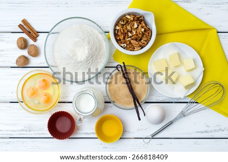 Baking cake in rural kitchen - dough recipe ingredients (eggs, flour, milk, butter, sugar) with yellow napkin on white wooden table from above.  - stock photo