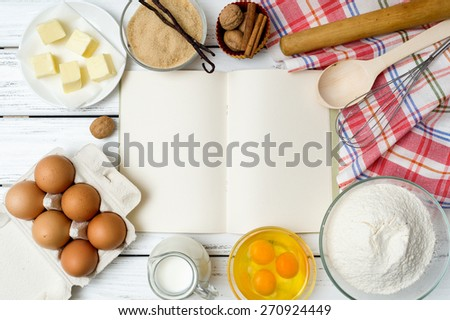 Baking cake in rural kitchen - dough recipe ingredients (eggs, flour, milk, butter, sugar) with recipe book, wooden spoon, whisk, rolling pin and kitchen towel on white wooden table from above. - stock photo