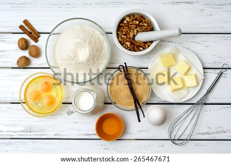 Baking cake in rural kitchen -  recipe ingredients (eggs, flour, milk, butter, sugar, walnuts, spices) on white wooden table from above.  - stock photo