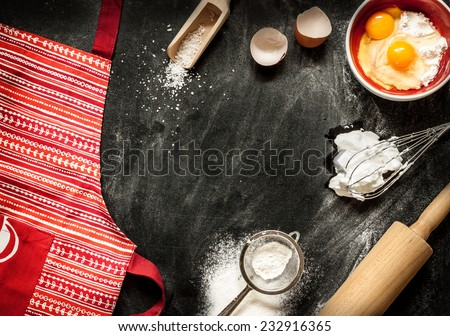 Baking cake ingredients. Apron, bowl, flour, eggs, egg whites foam, eggbeater, rolling pin and eggshells on black chalkboard from above. Cooking course poster background - layout with free text space. - stock photo