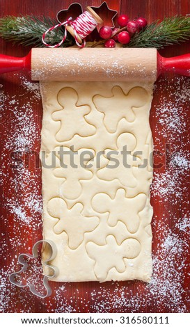 Baking Christmas cookies card. Rolling pin, cookie cutters, homemade dough and some ornament. - stock photo