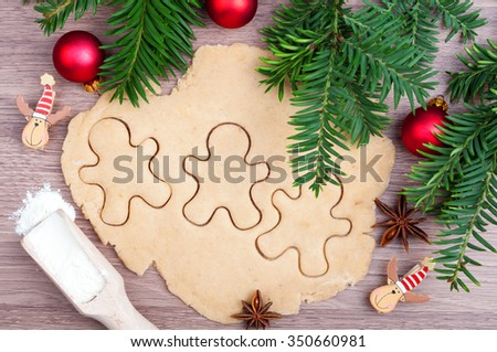 Baking Christmas cookies. Dough, gingerbread men, flour, anise star, Christmas tree and ornaments on the wooden background. Top view - stock photo
