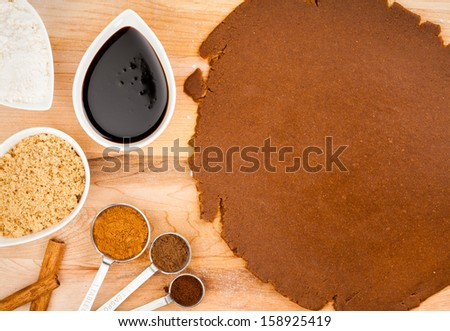 Baking Christmas Gingerbread cookies. Scene depicts rolled dough, spices, brown sugar, molasses, flour and cinnamon. - stock photo