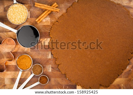 Baking Christmas Gingerbread cookies. Scene depicts rolled dough, spices, brown sugar, Molasses and gingerbread man cookie cutter. - stock photo