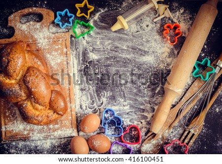 Baking concept on dark background. Baking cookies for children, top view of variety of baking utensils with bread, eggs and colorful cutters on black chalkboard. Children cooking. Top view.  - stock photo
