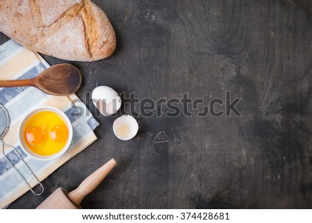 Baking dark background with blank cook book, eggshell, bread, flour, rolling pin. Ingredients for the baking. Rustic background with free text space - stock photo