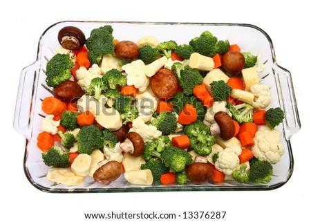 Baking dish with fresh chopped carrots, broccoli, cauliflower, parsnips and mushrooms. - stock photo