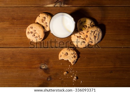 baking, eating, holidays and food concept - close up of oat cookies and glass of milk on wooden table - stock photo