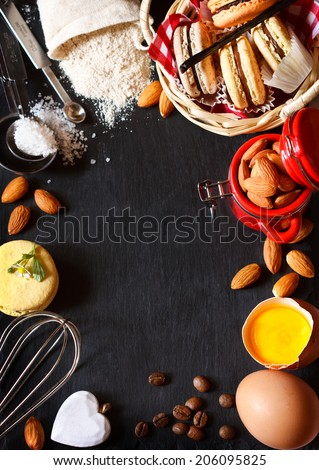 Baking frame. Sweet macarons cookies and food ingredients for baking on a black slate board with copy space for recipe. - stock photo