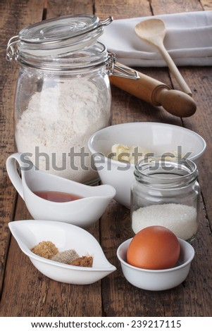 Baking gingerbread cookies. Ingredients and tools on vintage wooden table. Flour, butter, sugar, egg, spices.