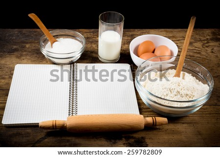 baking ingredients and blank cook book on rustic wooden table - stock photo