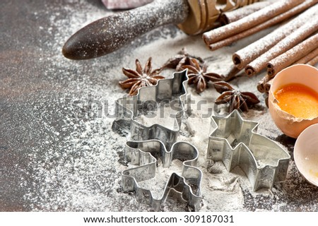 Baking ingredients and tolls for dough preparation. Flour, eggs, rolling pin and cookie cutters. Christmas food - stock photo