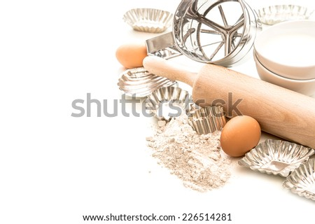 baking ingredients and tolls for dough preparation. flour, eggs, rolling pin and cookie cutters on white background - stock photo