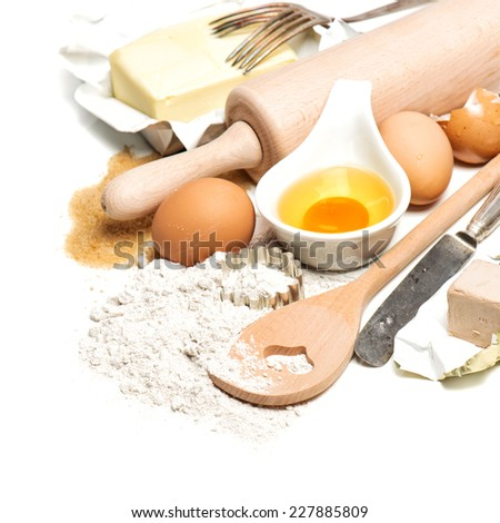 baking ingredients and tools for dough preparation. flour, eggs, sugar, butter, rolling pin and cookie cutters on white background - stock photo