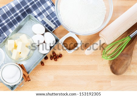 baking ingredients and tools from top with copy space on wooden background - stock photo