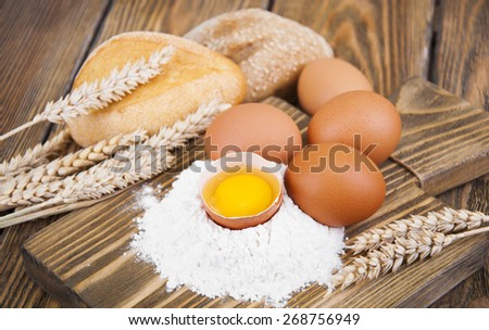 Baking ingredients - eggs, flour, and butter on a wooden background - stock photo