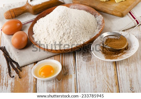 Baking ingredients - eggs, flour,  butter on  white  wooden background - stock photo