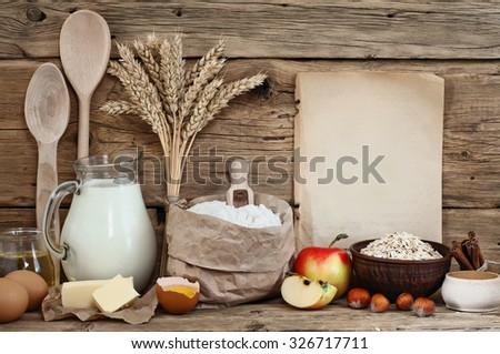 Baking ingredients (eggs, flour, milk, butter, sunflower oil, cinnamon, hazelnuts, apples, oatmeal flakes) on wooden background with a blank sheet. Top view. Free space for text. Food background - stock photo